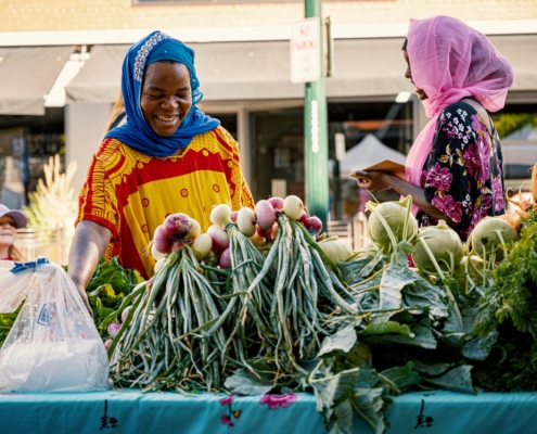Two women in front of a vegetable market